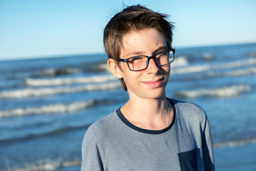 Young boy posing at the summer beach. Cute smiling happy 12 years old boy at seaside. Kid's outdoor portrait.