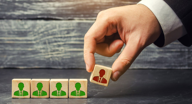 the businessman removes / dismisses the employee from the team. management within the team. wooden blocks with a picture of workers. control arm. leader. resignation