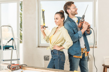 happy young couple holding tools and standing back to back during renovation