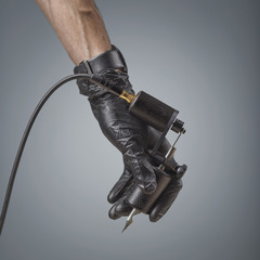 Tattooist hands in black gloves with tattoo machine isolated on gray background.