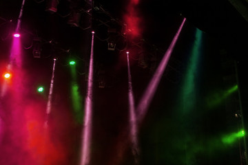 Stage lights. Several projectors in the dark. Multi-colored light beams from the stage spotlights...