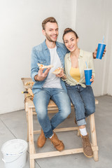 happy young couple with paper cups and pizza slices sitting together and smiling at camera in new apartment