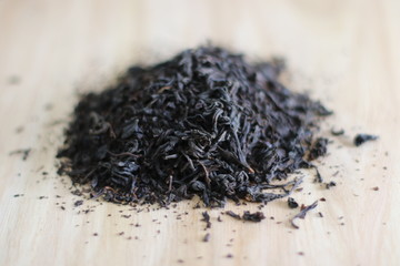 Dry black tea leaves on wooden table