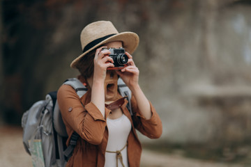 Active healthy Caucasian woman taking pictures with an vintage film camera on a forest rocks