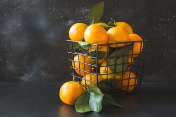 Fresh mandarins with leaves in modern bowl on black. Healthy eating concept. Copy space.