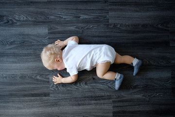 Upset baby in white bodysuit on the floor at home