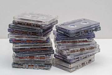 Stack of old dirty audio cassettes on the white shelf
