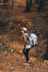 Woman in a stylish hat and travel bag on her shoulders, looking around at the charming autumn forest