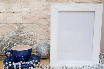 Blue cup of hot chocolate  and silver Christmas decoration. Free space for text.