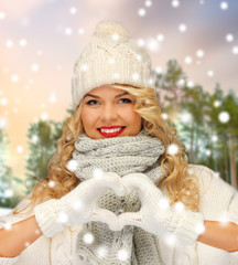 people, season and leisure concept - happy woman in hat, scarf and mittens showing hand heart over winter forest background