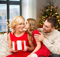 holidays, family and celebration concept - happy mother, father and daughter with gift at home over christmas tree lights background