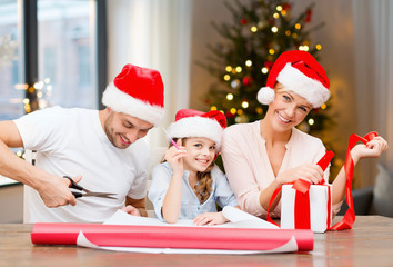 holidays, family and craft concept - happy mother, father and daughter wrapping gifts at home over christmas tree background