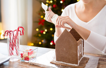 cooking, holidays and people concept - woman with pastry bag making gingerbread houses at home over christmas tree lights background