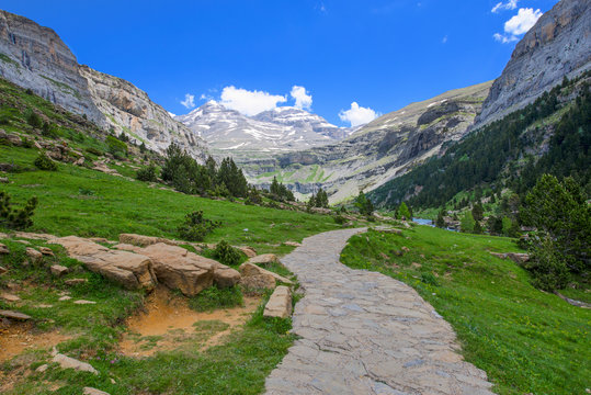 Road in the middle of a landscape of meadows with mountains in the background and on the sides. Landscape and nature.