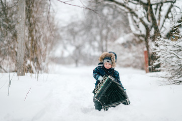 Young happy musician. Comic boy holding big heavy accordion. Lovely funny male kid carrying musician instrument on snowy winter road outdoor. Country lifestyle. Ridiculous baby cold nature portrait.