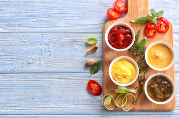 Different tasty sauces in bowls on light wooden table