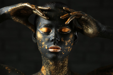 Foto op Aluminium Body Paint Beautiful woman with black and golden paint on her body against dark background