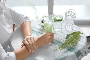 Woman with glass of fresh cucumber water at table