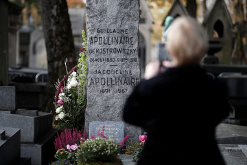 A woman takes pictures of the gravestone of French poet Guillaume Apollinaire during a ceremony to commemorate the centenary of his death at Pere Lachaise Cemetery in Paris