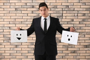 Businessman holding sheets of paper with drawn emoticons against brick wall