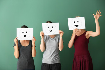 Young women hiding faces behind sheets of paper with drawn emoticons on color background
