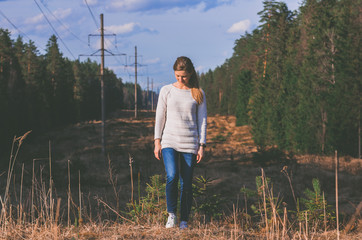Woman in white knitted sweater posing against the backdrop of a forest clearing in the countryside