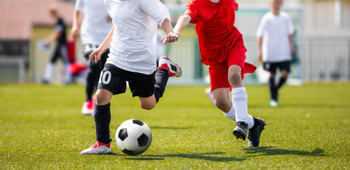 Two Young Boys in Soccer Sportswear Running and Kicking Ball on the Field. Low Angle Image of Youth Football Competition with Blurred Background