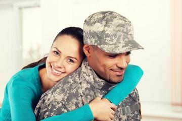 Happy woman hugging military man at home