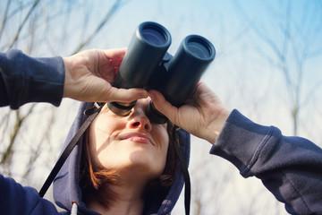 Fototapeta Girl with the field-glass watches birds. Ornithology. Birdwatching obraz