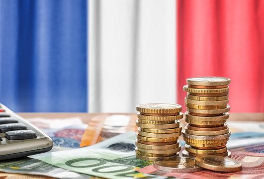 Geldscheine und Münzen vor der Nationalflagge Frankreichs