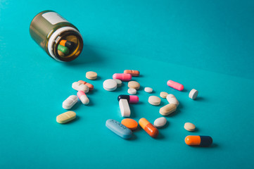 Multicolored isolated pills and capsules  on blue background