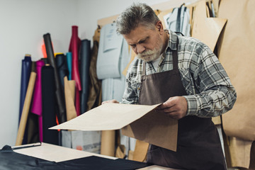 mature handbag craftsman in apron looking at cardboard at workshop