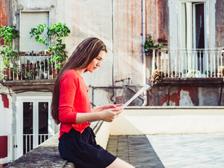 Cute woman holding a map, against the background of old houses in the beautiful city of Naples, Italy. Travel and tourism concept