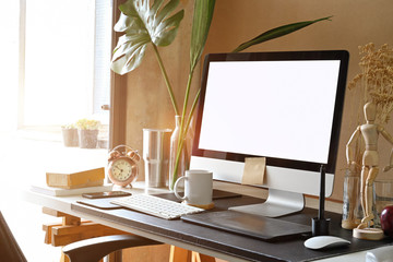 Creative workspace with desktop computer, empty poster frame on white work table.