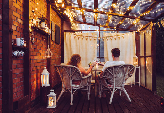 Young couple man and woman sit on white rattan garden chairs on wooden romantic outdoor terrace in the evening celebrating and toasting, spending time together. Candles burning in white lanterns.