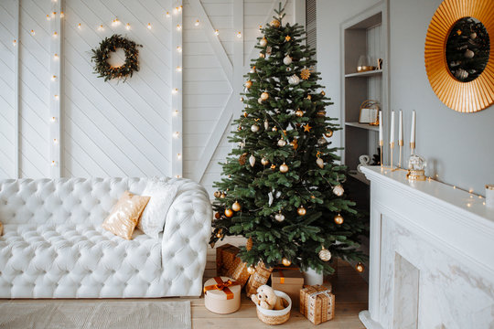 Christmas decor. Bright interior of the living room with large  elegant Christmas tree with toys and garlands  and white leather sofa