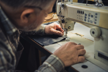 partial view off male handbag craftsman working on sewing machine at studio