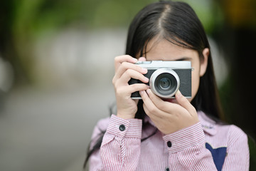 Girl taking pictures with a vintage camera.