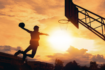 Basketball player performs a slam dunk