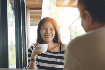 asians conversation friend concept.Women are raising their favorite coffee with a smile, Men and women are discussing about their work.