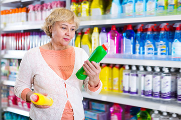 Cheerful woman choosing household chemical goods