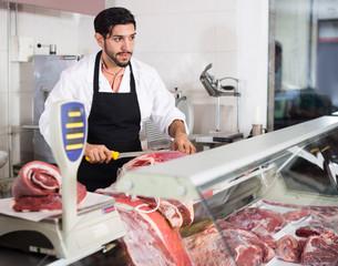 Adult man butcher cutting fresh meat