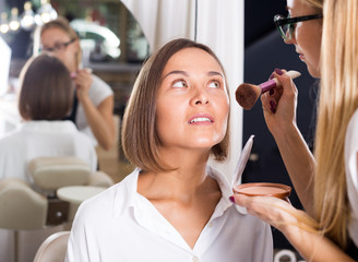 female makeup artist applying cosmetics for woman