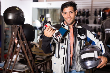 Young man in moto jacket is choosing new gloves