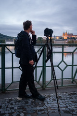 Thoughtful man in black clothing with camera and tripod waiting by a river to take a photo of Prague castle, Czech Republic.