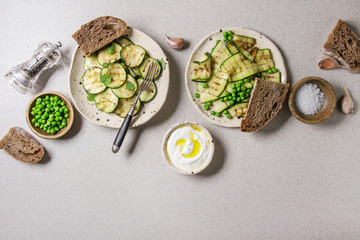 Variety of grilled zucchini salad with green pea, yogurt dip, garlic and rye sliced bread in spotted ceramic plates over grey background. Vegetarian food. Flat lay, space