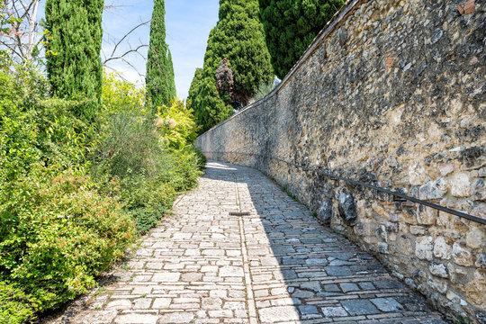 Via San Damiano street, road, stone walkway, path pedestrian way at monastery in Assisi, Italy with wall, old, ancient, antique architecture, Italian landscape, cypress trees in summer