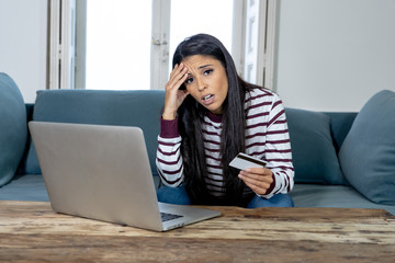 Young woman using laptop angry and stressed about her credit card bill
