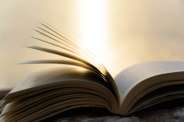 Open book with bright light on background, space for text