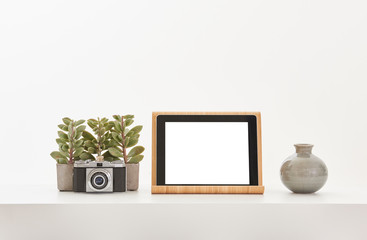 Tablet white screen camera vase of flower and ornament white table and white background.